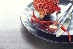El concepto del menú de la Navidad con las placas negras y los cubiertos adornó w Imagen de archivo libre de regalías