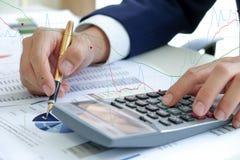 El concepto del negocio, la mano usando la calculadora y el control encierran señalar en fotografía de archivo libre de regalías