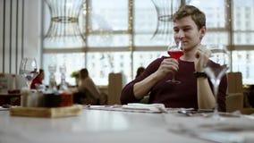 El concepto del restaurante: solamente manos, servicio y plato El camarero trae el vino de la orden en la bandeja de madera el ca almacen de video