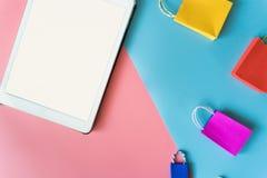El concepto en línea de las compras mínimas, el panier de papel colorido y la carretilla van abajo de la flotación Imagen de archivo