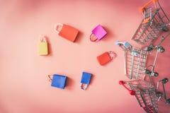 El concepto en línea de las compras mínimas, el panier de papel colorido y la carretilla van abajo de flotar el fondo rosado Imagen de archivo libre de regalías