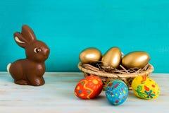 El concepto feliz de Pascua con oro del ANG del color eggs en cesta al lado del conejito de pascua del chocolate en fondo de made fotos de archivo libres de regalías