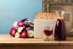 El concepto judío de la pascua judía del día de fiesta con el vino, el matzoh, la placa del vintage y la primavera florece Imágenes de archivo libres de regalías