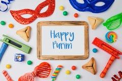 El concepto judío de Purim del día de fiesta con hamantaschen las galletas, la máscara del carnaval y el marco de la foto en el f fotos de archivo