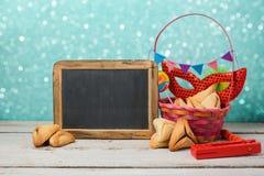 El concepto judío de Purim del día de fiesta con hamantaschen las galletas o los oídos de los hamans y la máscara del carnaval Foto de archivo
