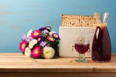 El concepto judío del día de fiesta de la pascua judía con el vino, el matzoh y la primavera florece sobre fondo de madera Imagen de archivo