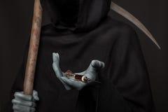 El concepto: matanza de las drogas Ángel de la muerte que sostiene la jeringuilla con heroína Imagenes de archivo