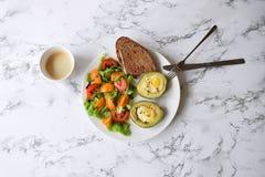 El concepto sano de la consumición coció el aguacate con los huevos de codornices imagen de archivo