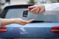 El concesionario de coches da a cliente las llaves del coche con el coche en backgorun Imagen de archivo libre de regalías
