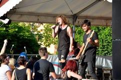 El concierto del aire abierto de la banda de la música rock llamó al paranoico El músico joven en negro disfruta del funcionamien Fotos de archivo libres de regalías