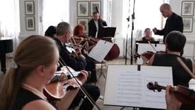 El conductor con la orquesta sinfónica, violinistas con las notas juega en sus instrumentos musicales dentro almacen de metraje de vídeo