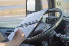 El conductor de camión está escribiendo en la documentación Fotografía de archivo