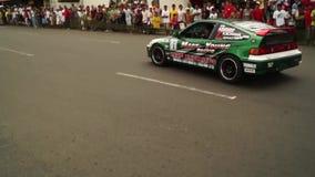 El conductor de coche de carreras encima dirige la rueda para acelerar el coche durante una competencia del coche de la deriva almacen de metraje de vídeo