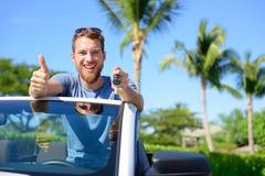 El conductor de coche que muestra llaves y los pulgares suben feliz Imagenes de archivo