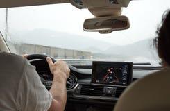 El conductor de coche sostiene el volante y monta por la navegación GPS imagenes de archivo