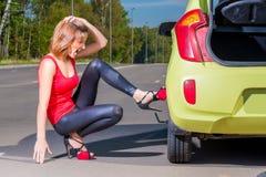 El conductor de la muchacha intenta substituir la rueda pinchada Fotos de archivo