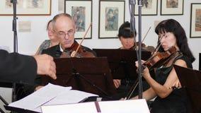 El conductor de la orquesta, violinistas juega música clásica y mira en la hoja de papel con las notas musicales metrajes