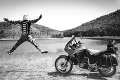 El conductor de motocicleta salta con sus brazos extendidos para una reunión de aventuras en el río de la montaña de la playa  foto de archivo libre de regalías