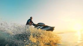 El conductor de un watercraft está flotando en él a lo largo de la reserva de agua durante puesta del sol metrajes