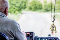 El conductor del autobús maneja con confianza un vehículo, montando en r rural imagenes de archivo