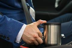 El conductor en el coche toma una taza del termo con una barra de café para no caer dormido en la rueda fotos de archivo