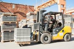 El conductor en el camión de elevación carga productos de la planta Fotos de archivo