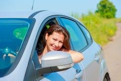 El conductor femenino mira hacia fuera la ventanilla del coche fotos de archivo