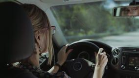 El conductor femenino se refleja en espejo de la vista posterior del coche almacen de metraje de vídeo