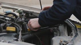 El conductor fija el malfuncionamiento del coche Capilla aumentada Vista del motor, los tapones de la batería y de relleno y los metrajes