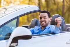 El conductor latinoamericano negro joven que sostiene el coche cierra la conducción de su n Foto de archivo