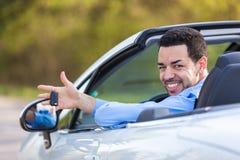 El conductor latinoamericano negro joven que sostiene el coche cierra la conducción de su n Imagen de archivo