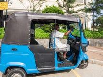 El conductor mayor del pasajero que espera del taxi de tres ruedas para durante el día soleado Fotos de archivo
