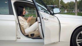 El conductor moreno bastante elegante de la mujer de negocios de los jóvenes comunica por el teléfono en el estacionamiento, meca almacen de metraje de vídeo