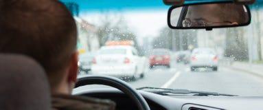 El conductor observa el camino de ciudad del volante de la conducción de automóviles dentro Imagen de archivo libre de regalías