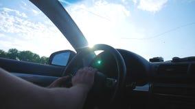 El conductor que conduce el coche monta a lo largo del camino, los rayos brillantes del brillo del sol Perfil de las impulsiones  metrajes