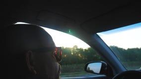 El conductor que conduce el coche monta a lo largo del camino, los rayos brillantes del brillo del sol Perfil de las impulsiones  almacen de metraje de vídeo
