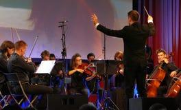 El conductor que dirigía a la orquesta sinfónica con los ejecutantes en fondo durante la ceremonia de inauguración del negocio sa imagenes de archivo