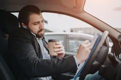 El conductor que va en el camino, hablando en el teléfono, trabajando con los documentos al mismo tiempo Hombre de negocios que h imagen de archivo libre de regalías