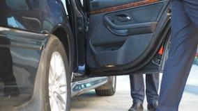 El conductor que viene al coche y abre la puerta para el hombre de negocios El chófer destapa la puerta del automóvil para el pas metrajes