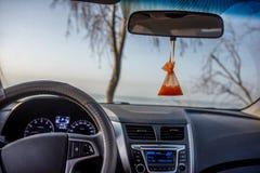 El conductor se sienta en el coche y mira hacia fuera la ventana Él condujo para arriba al lago en la puesta del sol o la salida  fotografía de archivo libre de regalías