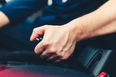 El conductor tira de la palanca del freno de mano Mano masculina que tira del freno de estacionamiento usando la palanca del fren Fotos de archivo libres de regalías