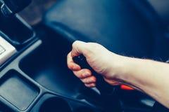 El conductor tira de la palanca del freno de mano Mano masculina que tira del freno de estacionamiento usando la palanca del fren Imágenes de archivo libres de regalías