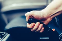 El conductor tira de la palanca del freno de mano Mano masculina que tira del freno de estacionamiento usando la palanca del fren Foto de archivo libre de regalías