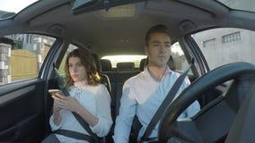 El conductor y la novia utilizan los teléfonos elegantes y mandar un SMS mientras que conduce y no presta la atención al camino - almacen de video