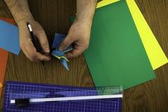 El conejito de papel para Pascua, manos hace papiroflexia del papel coloreado, copia-goma de la lección de la papiroflexia foto de archivo libre de regalías