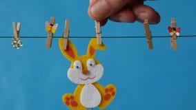 El conejito de pascua está colgando en la cuerda para tender la ropa en fondo azul