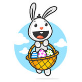 El conejito de pascua feliz sostiene la cesta con los huevos Foto de archivo