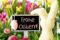 El conejito de pascua, flores coloridas de la primavera, Frohe Ostern significa Pascua feliz Fotos de archivo libres de regalías