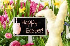 El conejito de pascua, flores coloridas de la primavera, manda un SMS a Pascua feliz Foto de archivo libre de regalías