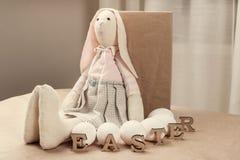 El conejito del juguete de Pascua, huevos blancos, reserva la palabra PASCUA por las letras de madera Foto de archivo